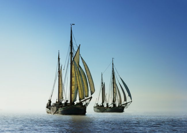 Back light image of two traditional sailing boats under sail, sailing on the ocean. Adventure concept. Reaching for new shores.